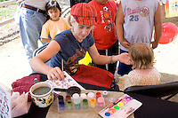Face painter applying her trade to a young model. Dragon Festival Lake Phalen Park St Paul Minnesota USA