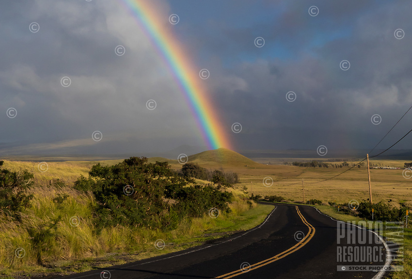 A powerful rainbow seems to touch a pu'u (hill or mound) near a road going through Kamuela (a.k.a. Waimea), Big Island of Hawai'i.