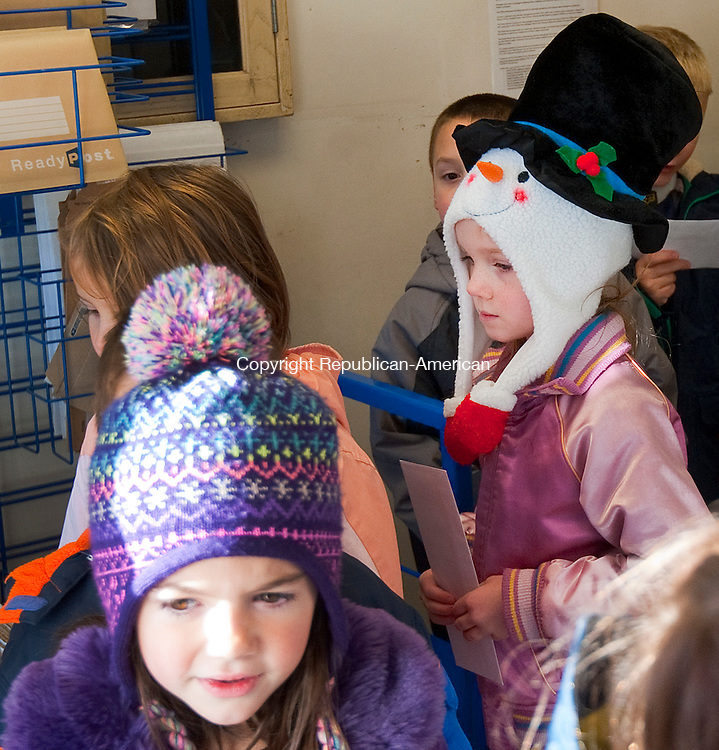 PLYMOUTH, CT--- -120315JS04--Kierdin Ireland, right, a first grade student at Plymouth Center School, along with her classmates, drop off their letters to Santa during their annual visit to the Plymouth Post Office on Thursday. The children also received a tour of the post office and a gift bag. <br /> Jim Shannon Republican-American