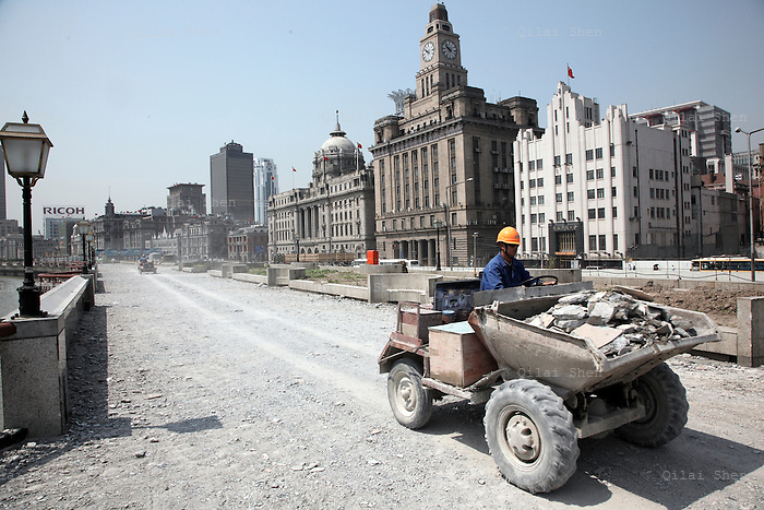 With the historical architecture of the older banks, custom houses, and hotels from Shangh's concession days in the background, a worker drives a tractor through a construction site, a part of the historical riverside Bund renovation project underway for the upcoming World Expo in Shanghai, China on 27 May 2009.  60 years ago today residents of Shanghai woke up to find communist soldiers sleeping on the streets as the People's Liberation Army drove away the defending Nationalists after 15 days of intense fighting using only light weaponry to minimize collateral damage.