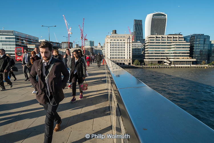 City of London workers cross London Bridge at the start of the evening rush hour
