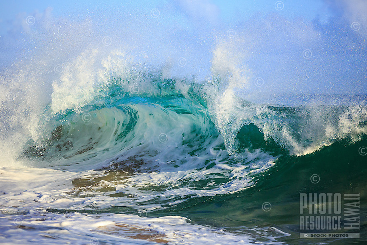 A giant wave curls into various shades of blue at Secrets Beach, Kaua'i.