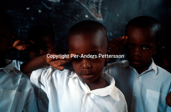 KINSHASA, CONGO - FEBRUARY 28: Unidentified boys during the singing of patriotic military song in their class on February 28, 2002 at ÒBambiniereÓ a school in Lingwala district, in Kinshasa, Congo. The teacher tells them about the occupation of Rwandan and Ugandan troops in the country..Photo: Per-Anders Pettersson/ Getty Images.....