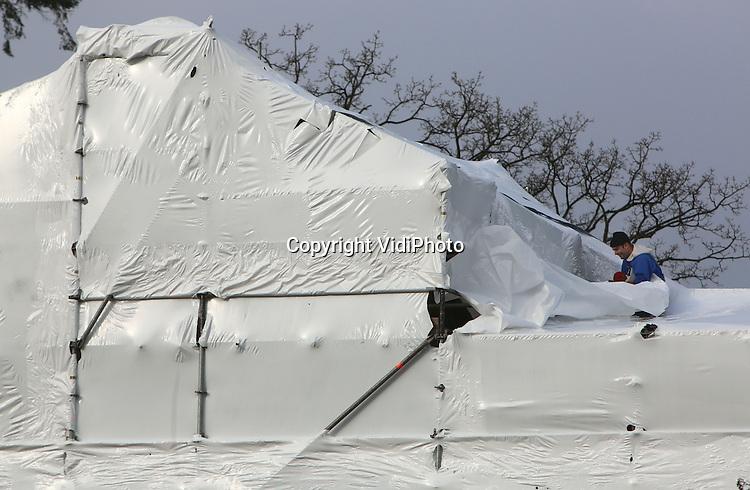 Foto: VidiPhoto<br /> <br /> ARNHEM - Inpakken en wegwezen. De kasteelboerderij van het Nederlands Openluchtmuseum wordt vrijdag door steigerbouwers in plastic verpakt voor een ingrijpende renovatie. Nog voor de start van het nieuwe seizoen moet het dak van het voorhuis van de boerderij vernieuwd worden. Daarnaast worden er werkzaamheden uitgevoerd aan het metselwerk. Om tijdens kou, sneeuw en vorst door te kunnen werken, wordt het hele voorhuis in plastic verpakt. Hoofdaannemer is de firma Hoffman uit Beltrum. Op 27 maart moet de restauratie klaar zijn.