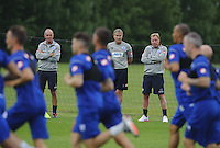 QPR manager Harry Redknapp watches his team train with assistants Kevin Bond and Joe Jordan
