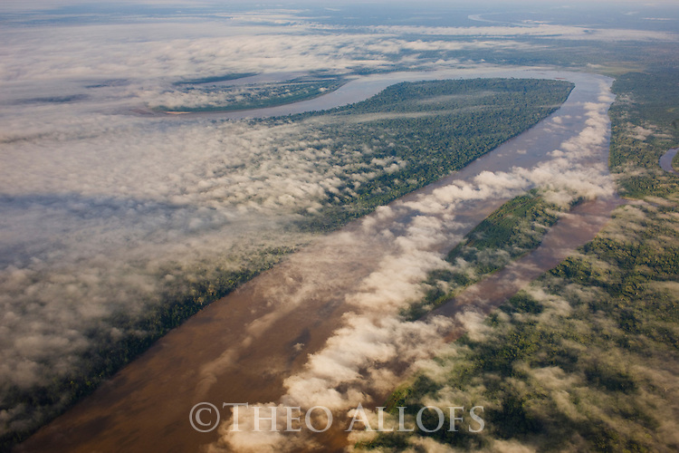 Bolivia, Beni Department, aerial view of Madre De Dios River winding through pristine Amazonian rainforest, morning fog