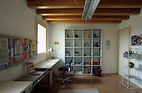 An open book shelf stands at one end of the studio which is furnished with a long desk designed by Jacques Toissant