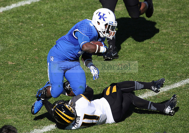 Kentucky Wildcats running back Raymond Sanders (4) gets tackled by Missouri Tigers defensive back Aarion Penton (11) during the first half of the University of Kentucky vs. Missouri University football game at Commonwealth Stadium in Lexington, Ky., on Saturday, November 9, 2013. Mizzou led 28-3 at the half. Photo by Tessa Lighty | Staff