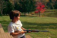 Young boy wearning Nonviolence t-shirt stands fiercely as he aims his BB gun