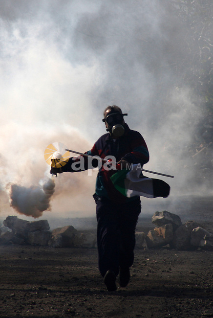 A palestinian demonstrator throws back a tear as canister  fired by Israeli soldiers during clashes at the weekly protest against the Jewish settlement of Qadomem, near Nablus, West Bank, 28 December 2012. According to Palestinian sources, five demonstrators were wounded during the clashes. Photo by Nedal Eshtayah