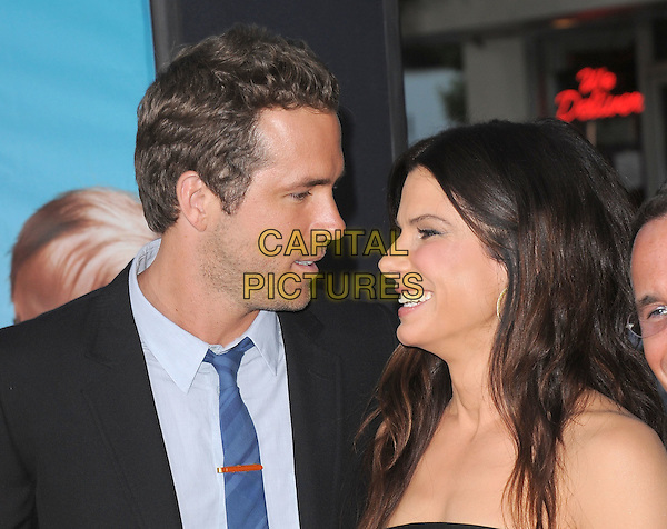 "Ryan Reynolds & Sandra Bullock .The Universal Pictures' L.A. Premiere of ""The Change-Up"" held at The Village Theatre in Westwood, California, USA..August 1st, 2011                                                                                .headshot portrait black strapless blue tie stubble facial hair profile smiling .CAP/RKE/DVS.©DVS/RockinExposures/Capital Pictures."
