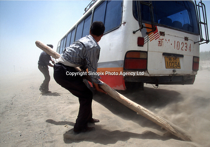 In the middle of the Taklamahan desert in Xinjiang, a bus passenger uses a wooden pole trying to give the bus more traction during a sand storm..18-AUG-00