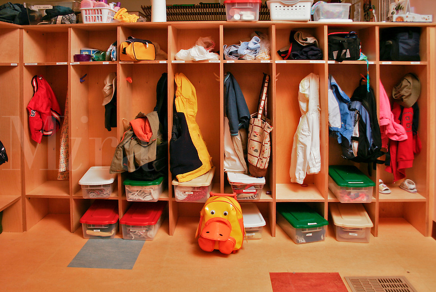 Preschool classroom cubbies with coats and backpacks.