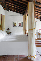 The master bedroom is a cool and relaxing space decorated in white and neutral. Traditional local materials were kept during the restoration of the house, such as the terracotta tiles on the floor and ceilings and the original massive wooden beams.