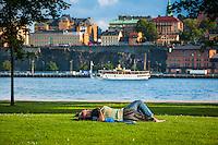 Par ligger på en gräsmatta på Skeppsholmen i Stockholm