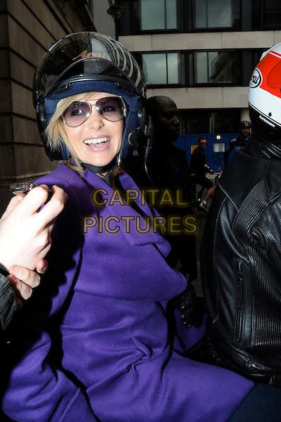AMANDA HOLDEN .Leaving BBC Radio 2 studios, .London, England, UK, .October 2nd 2010..half length purple coat  motorbike motorcycle helmet sunglasses smiling aviators .CAP/IA.©Ian Allis/Capital Pictures.