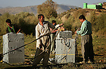 Still on the Iraqi side before crossing, Iranian Kurdish smugglers rig up the packs they use to carry televisions and other electronic goods from Iraq into Iran in full view of the Iranian border fort in the background on Wed. Sept. 20, 2006.