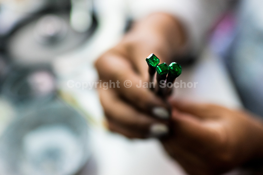 An emerald cutter shows a gemstone she is working on in a cutting and polishing workshop in Bogota, Colombia, 31 January 2013. Approximately 60 percent of the world's total amount of emeralds come from Colombia. Most of the rough gems are processed in workshops located in the emerald district in downtown Bogota. Due to their special clarity and deep vivid green color, Colombian gemstones are considered the most beautiful emeralds in the world.