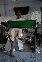 INDIA Madhya Pradesh , children work in ginning factory where cotton fibre is separated from seed / Indien Madhya Pradesh Mandleshwar , Kinder stopfen Rohbaumwolle in die Entkernungsmaschinen in einer Fabrik um Faser vom Samen zu trennen