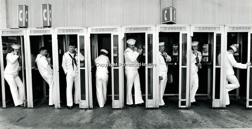 Sailors just off the Aircraft Carrier USS Carl Vinson hit the phone booths on the dock at Naval Air Station Alameda, California..(1993 photo by Ron Riesterer)