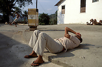 Left idle when work and educational programs on the farm are scarce, residents of the Fazenda Modelo relax in the sun along a street in the more than 100-acre complex, while boys shoot soccer balls at a wall nearby. Though residents are free to leave the shelter, it is a nearly 70-kilometer trek back to the city streets.