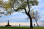 The Chicago Lakefront Trail And Joggers Framed By Foreground Trees With Lake Michigan In The Background, Chicago Illinois, USA