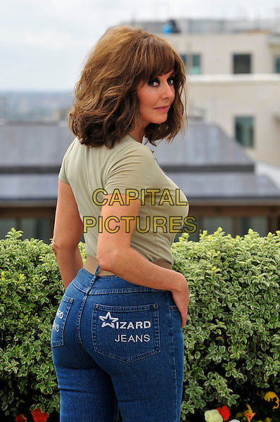 "Carol Vorderman.Winner of the Female ""Wizzard Jeans"" Rear of the Year 2011, Dorchester Hotel, London, England..June 8th, 2011.half length jeans denim beige top belt  back behind looking over shoulder.CAP/CJ.©Chris Joseph/Capital Pictures."