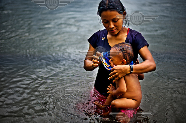 Jacqueline feeds one of her children in a river.