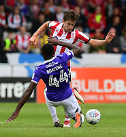Lincoln City's Alex Woodyard vies for possession with Exeter City's Hiram Boateng<br /> <br /> Photographer Chris Vaughan/CameraSport<br /> <br /> The EFL Sky Bet League Two Play Off First Leg - Lincoln City v Exeter City - Saturday 12th May 2018 - Sincil Bank - Lincoln<br /> <br /> World Copyright &copy; 2018 CameraSport. All rights reserved. 43 Linden Ave. Countesthorpe. Leicester. England. LE8 5PG - Tel: +44 (0) 116 277 4147 - admin@camerasport.com - www.camerasport.com