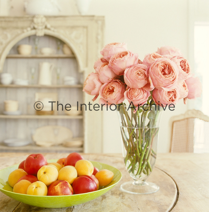 A vase of pink peonies and a bowl of fruit grace the 19th century wine-tasting table in the dining room