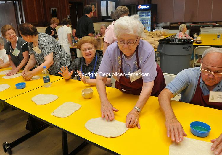 WATERBURY, CT-15 JULY 2010-071510IP02- (from right) Ed and Gertrude Brouillard, Dolores Lamontagne, Giusephina LaPorta and Louisa Sica stretch out dough to make fried dough during the Our Lady of Mount Carmel Feast in Waterbury on Thursday. Fried dough is a big seller at the festival and 3,500 lbs. of dough are used throughout the four-day event to make it. The festivities at Our Lady of Mount Carmel Church, which include food, live entertainment, and kids' activities, will run through Sunday. <br /> Irena Pastorello Republican-American