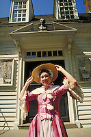 woman posing at Williamsburg Colonial Historic Park wearing period costume and hat. woman. Williamsburg Virginia.