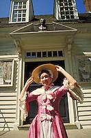 woman posing at Williamsburg Colonial Historic Park wearing period costume and hat. woman. Williamsburg Virginia.
