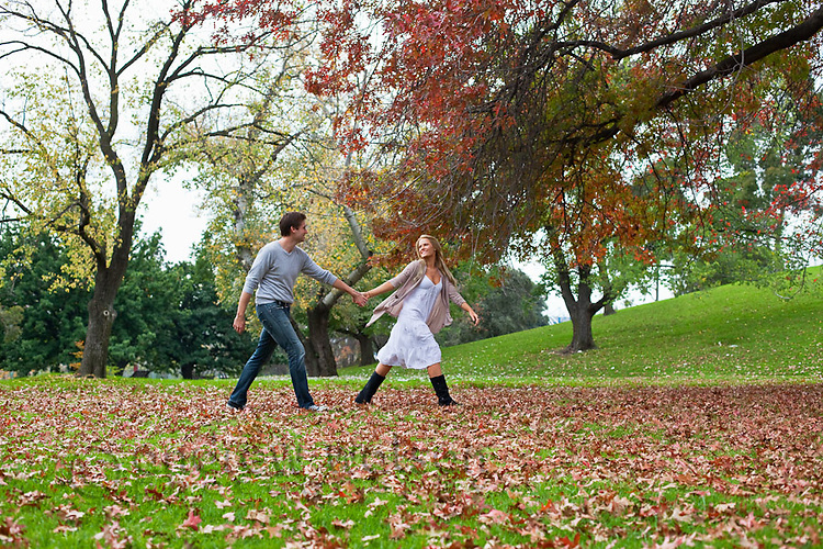 Young couple walking through leaves in park, holding hands.  Melbourne, Victoria, Australia