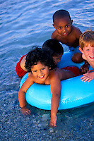 Four boys playiing at the beach with a inner tube