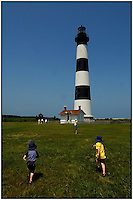 Two young boys run to see the Bodie Island Light House in the North Carolina Outer Banks. Photo is model released.