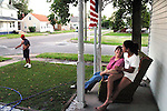 """This is the American dream and we are living it,"" said Marisela Chavez, enjoying a quiet summer evening with Stephanie, 11, one of her three daughters. Chavez came to Beardstown in 1995; she works for the school system's bilingual program and her husband Valentine, left, works at Excel. Like many Mexican families in Beardstown, they purchased a home next to Caucasian neighbors and adopted local customs, such as flying the flag and maintaining their lawn...Kristen Schmid Schurter/SJ-R"