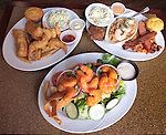 The Gulf Shores Restaurant & Grill in Edwardsville is the second location of the popular Cajun-themed eatery which has another site in St. Louis. This location is within the Edwardsville Crossing shopping complex. In the center foreground is the Buffalo Shrimp Salad, with Romaine and field greens tossed with grape tomatoes, cucumbers, red onions and cheese. The jumbo battered shrimp are coated with Gulf Shores' own blend of Frank's Red Hot Sauce and Cajun seasonings. It's served with homemade Cajun Ranch dressing. In background are the Seaside Combo (left) and Bourbon Street combo.