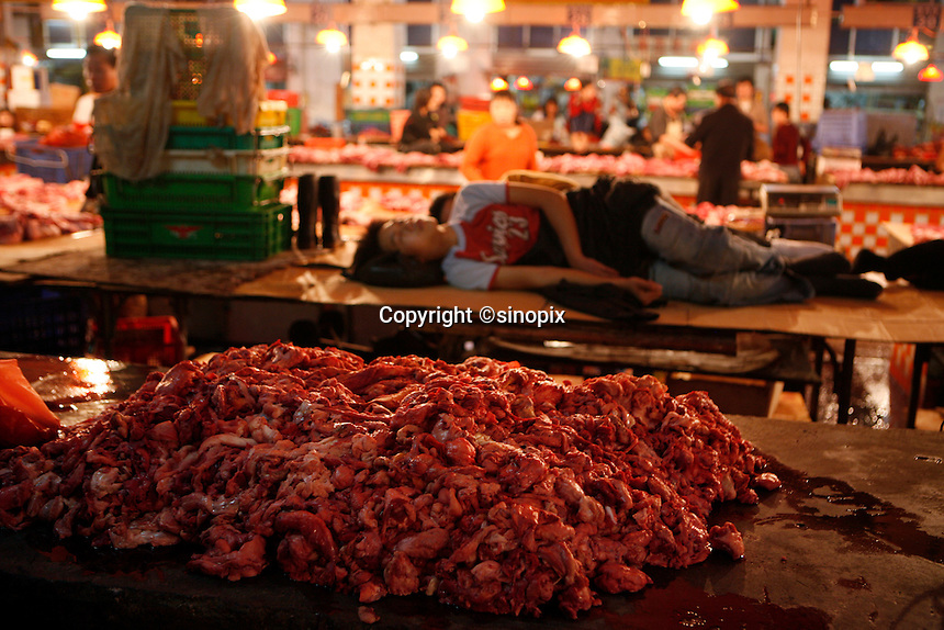 A boy sleeps on a counter near a pile of waste meat in the Shenzhen Buji agricultural market.<br />
