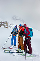 Ski tourers stand looking at a phone map while navigating a storm during the Öztal ski tour, Austria