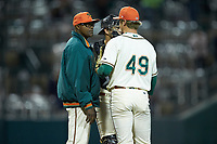 Greensboro Grasshoppers pitching coach Stan Kyles (50) has a meeting on the mound with relief pitcher Nick Mears (49) and catcher Zac Susi (45) during the game against the Hagerstown Suns at First National Bank Field on April 6, 2019 in Greensboro, North Carolina. The Suns defeated the Grasshoppers 6-5. (Brian Westerholt/Four Seam Images)