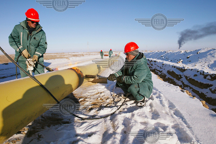 Workers lay an oil pipeline for Hurricane Kumkol Munai (formerly the state-owned oil company, Yuzhneftegazin, until it was taken over by Hurricane Hydrocarbons).
