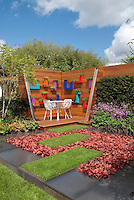 Small privacy deck with wall of hanging modern planters of herbs, with lawn grass rectangles and Heuchera plants in flower, with stone walk patio, sunny blue sky and puffy white clouds, white patio furniture, garden with flowers, hedge, birch trees Betula