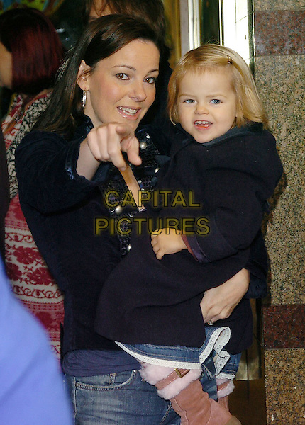 """RUTHIE HENSHALL & DAUGHTER.""""Noddy & the Island Adventure"""" charity dvd screening, London, UK..October 23rd, 2005.Ref: CAN.half length pointing gesture carrying child mother family.www.capitalpictures.com.sales@capitalpictures.com.©Can Nguyen/Capital Pictures"""