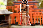 Closeup of a rope of Suzu, Japanese Shinto shrine bell with Offering written on it at Fushimi Inari shrine in Kyoto, Japan.