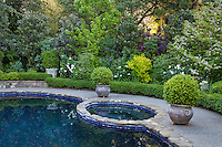 Swimming pool and hot tub flanked by containers on stone walkway with shrub border tapestry; Scales garden