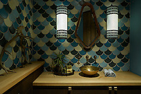 A small cloakroom is decorated with geometric wall tiles