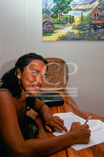 Altamira, Amazon, Brazil. Smiling woman writing on a printed page with telephone and painting on the wall.