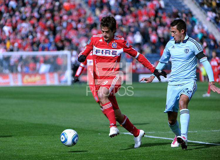 Chicago Fire forward Diego Chaves (99) dribbles away from Sporting KC midfielder Davy Arnaud (22).  The Chicago Fire defeated Sporting KC 3-2 at Toyota Park in Bridgeview, IL on March 27, 2011.