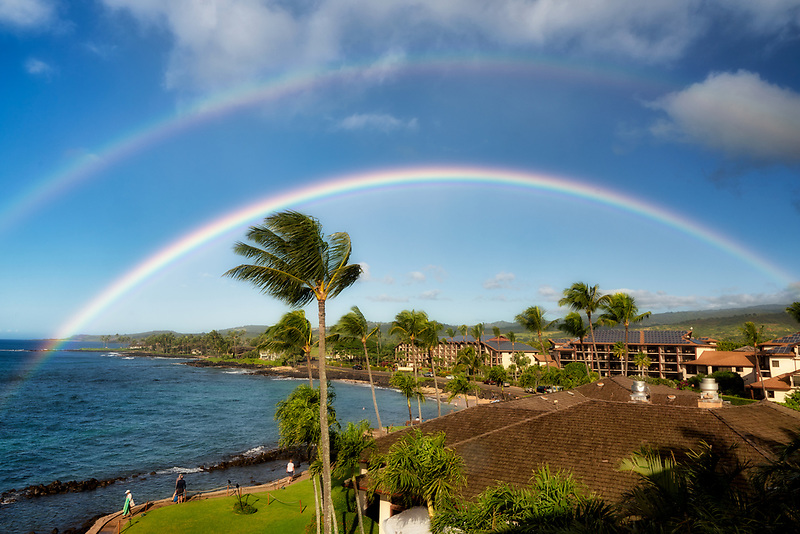 View of ocean front resorts with rainbow in Poipu, Kauai, Hawaii